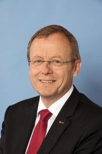 Smiling man with glasses in suit.