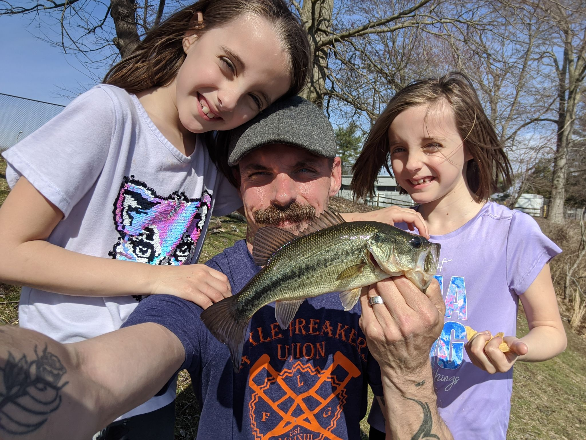 Man and two little girls. He is holding a fish.
