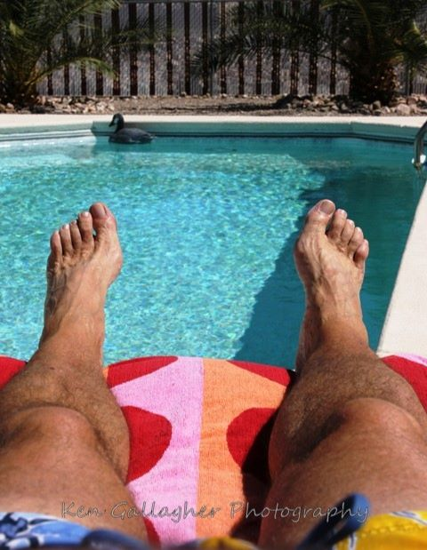 View of swimming pool past man's bare feet.
