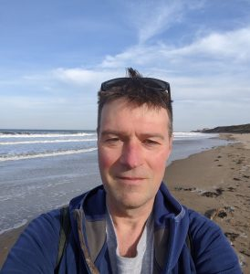 Man with seashore in background under blue sky.