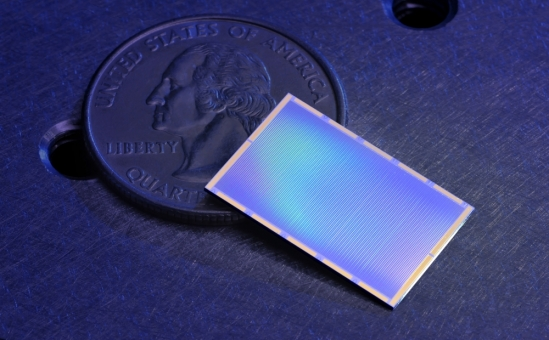 Shiny blue, thin, flat rectangular object on top of a U.S. quarter coin.