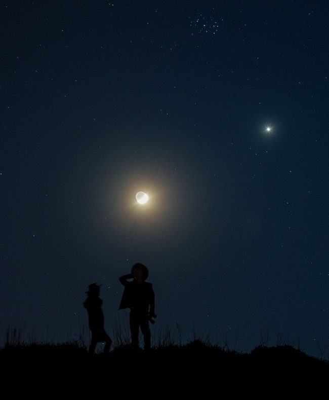 Two silhouetted people standing under a night sky with moon, Venus, and Pleiades.