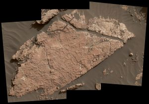 Brownish rock with cracks surrounded by sand.