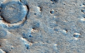 Grayish and bluish terrain with craters and hills.