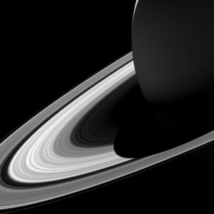 Large sphere in shadow surrounded by rings on black background.