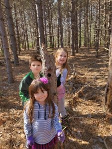 Three children in the woods.