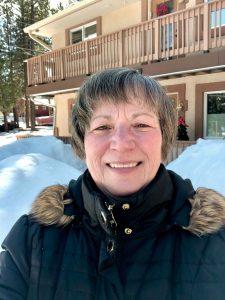 Smiling woman outside in snowy scene.