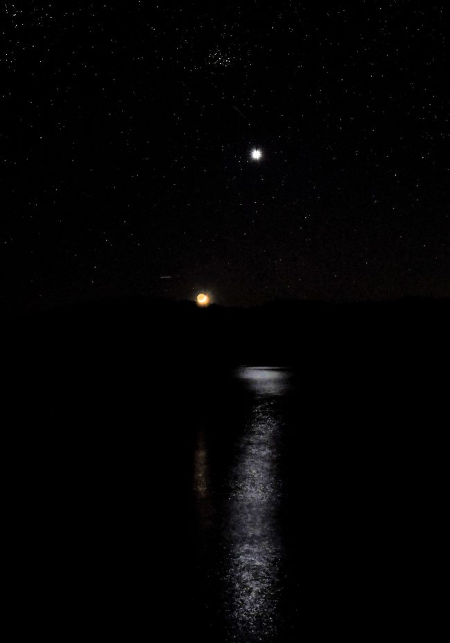 Moon, Venus, and Pleiades over a body of water.