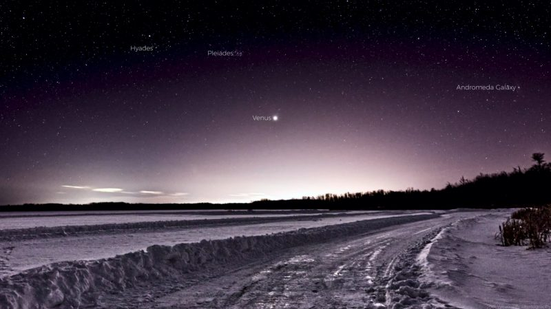 A frozen road, snow piled up on either side, with Venus above.