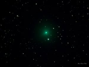A fuzzy green comet in front of the stars.