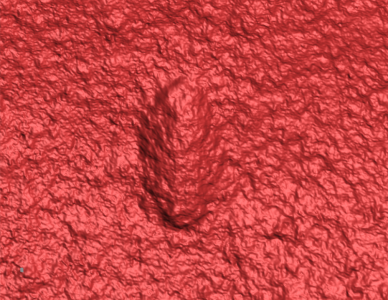 Red textured surface with an oblong impression in it.