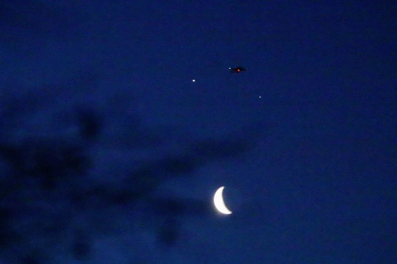 Planets, moon, distant plane with tiny red and green lights.