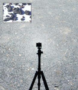 A tripod set up to photograph volcanic gravel.