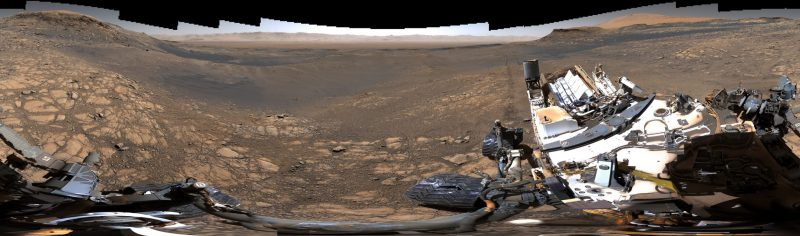 Rocky landscape in background with parts of rover visible up close.
