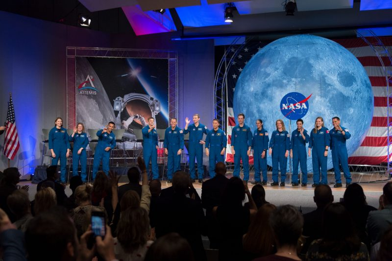 A line of men and women in blue jumpsuits standing on a stage with big NASA pictures behind them.