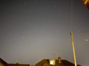 Stars and the bright planet Venus, in a well-lit suburban sky.