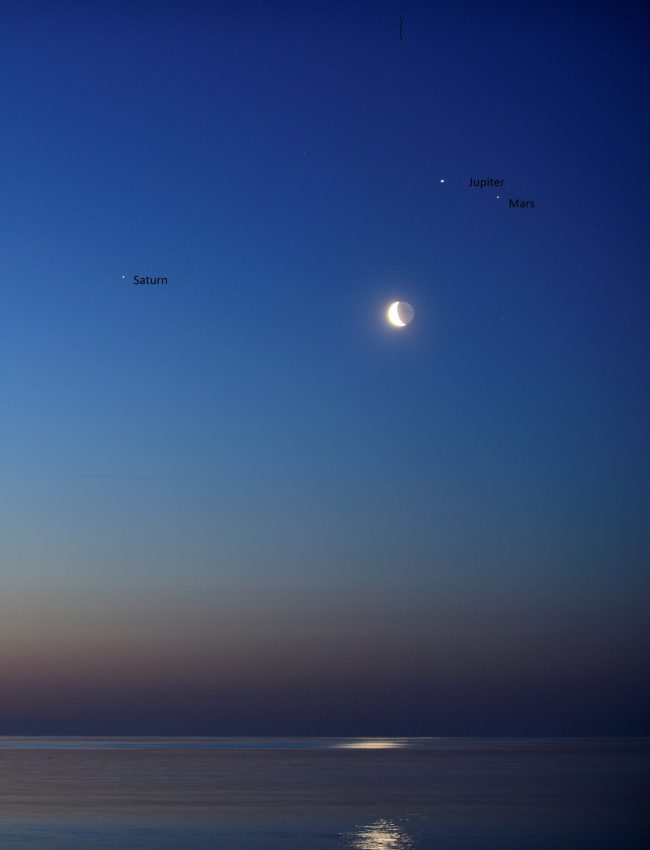 Planets and moon in dawn sky, over water with reflection of moon in water.