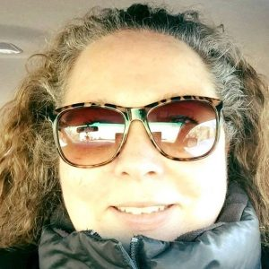 Woman in sunglasses and a parka.