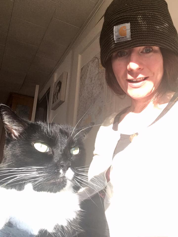 Woman in knit cap with a black-and-white cat.