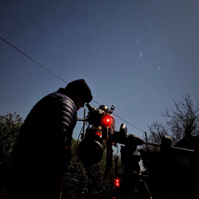 Man in winter clothing at a small telescope, under the night sky.