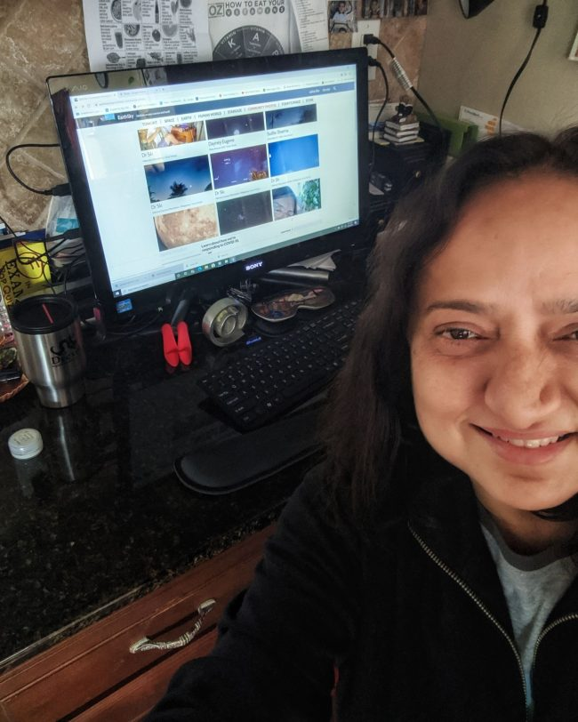 Smiling woman in front of a computer open to EarthSky Community Photos.