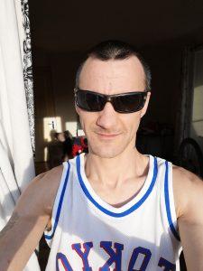 Man in sunlight, in a muscle shirt.