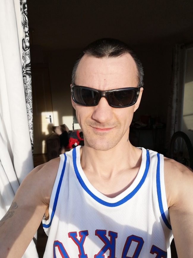 Man in sunlight, in a muscle shirt.