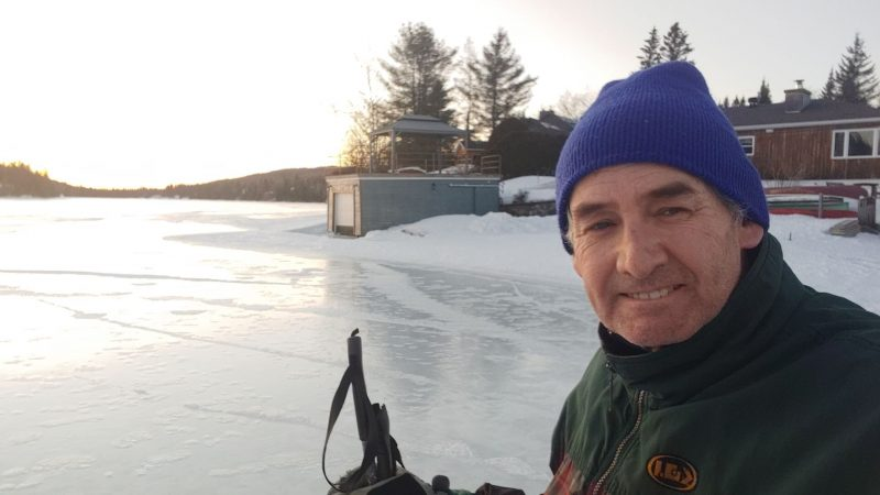Man standing in front of a shiny, flat frozen lake.