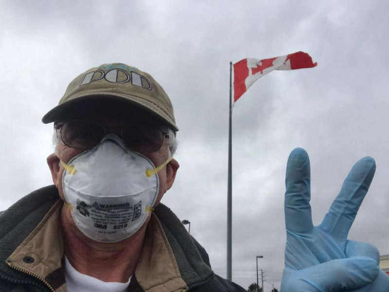 Man in face mask and latex gloves making a V sign, in front of Canadian flag flying from a tall flagpole.