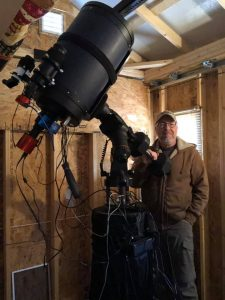 Man standing in front of a telescope.
