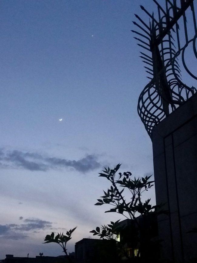 Small moon far below Venus in twilight.
