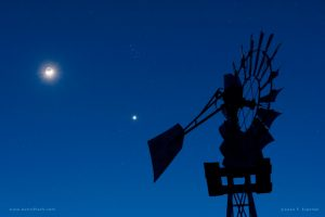 Waxing crescent moon, bright Venus, dipper-shaped Pleiades star cluster with a windmill in the foreground.