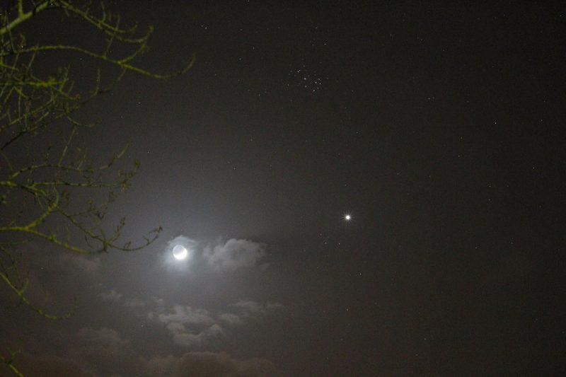 Waning moon, Venus and Pleiades among wispy clouds.
