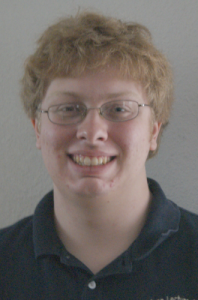Smiling man with eyeglasses in polo shirt.