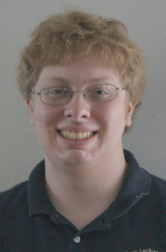 Smiling young man with eyeglasses, wearing a polo shirt.