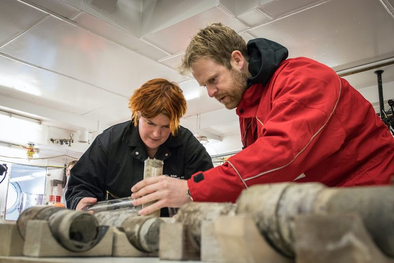 Two scientists working on a sediment core sample which has a long cylindrical shape.
