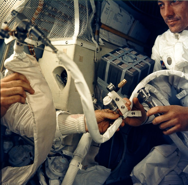 Astronauts and tubing and equipment in cramped space.