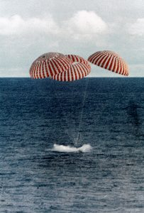 Ocean with object splashing in water, three parachutes above.