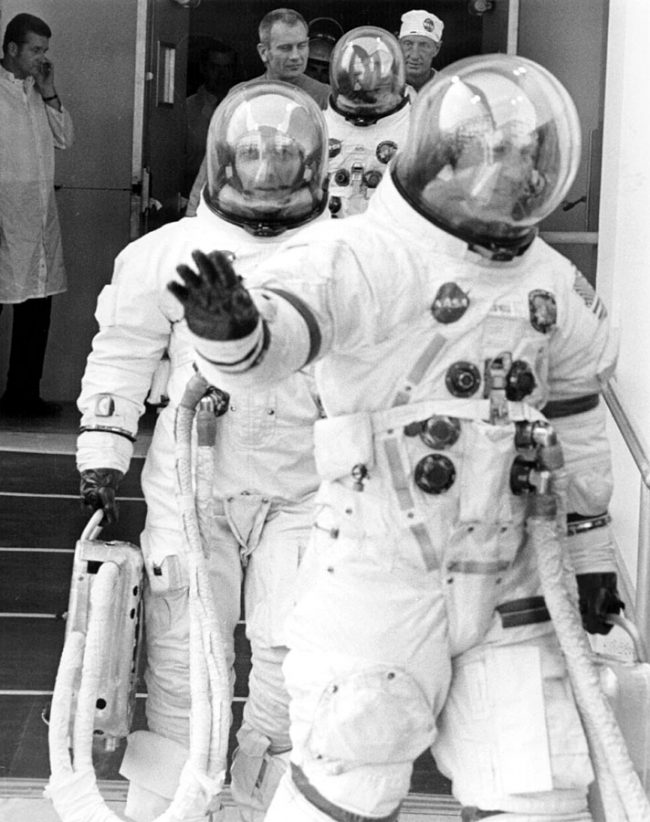 Suited up astronauts walking, one of them waving to camera.