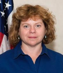 Red-haired woman in blue shirt in front of flag.