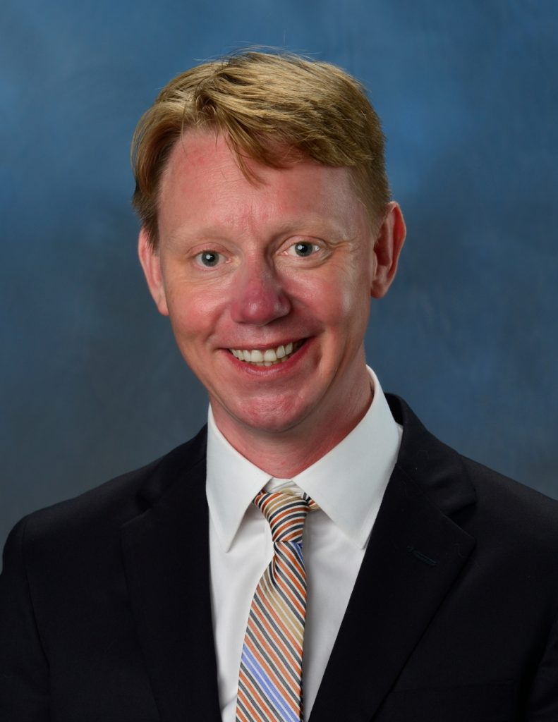 Smiling man in suit on blue background.