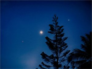 Crescent moon with two bright dots.