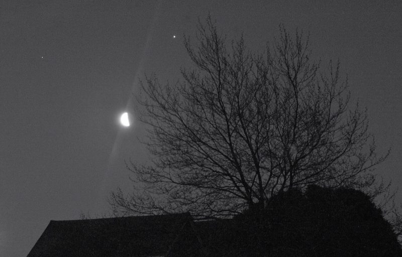 Moon with light streaks and 2 planets with a bare tree over a rooftop in foreground.