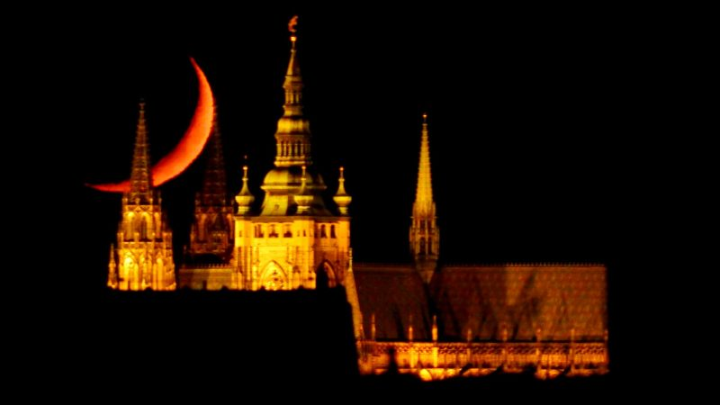 Orange crescent moon behind ancient pointy towers at night.
