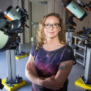 Woman with eyeglasses and telescopes behind her.
