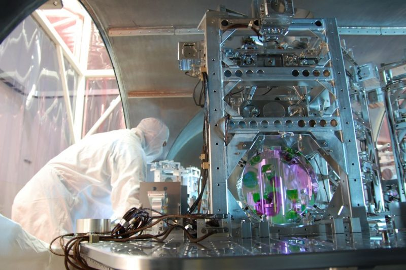 A man in a white coat and mask, working at an enormous machine with a metal frame and glass tubes.