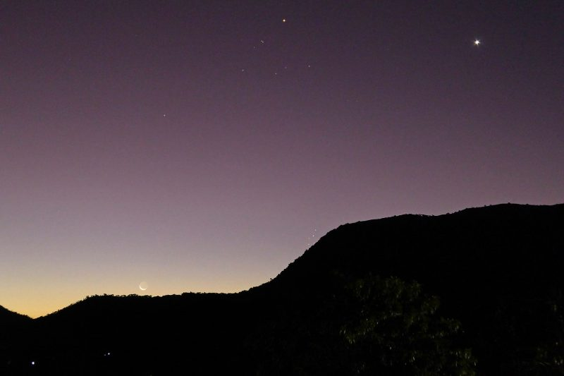 Tiny crescent moon over dark hill with bright Venus above.
