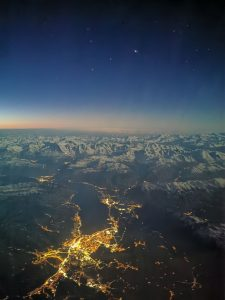 Aerial view of corrugated mountains with three planets in the sky and a lit up city below.