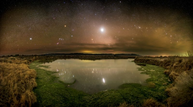 Bright Venus among stars over a desert landscape, reflected in a pool of water.