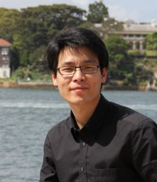 Smiling man with eyeglasses in front of lake.